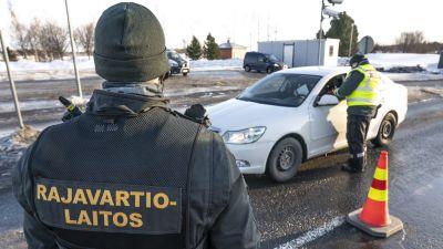 Gränsbevakare i tjocka overaller granskar en personbil på gränsen mellan Sverige och Finland i Torneå och Haparanda.
