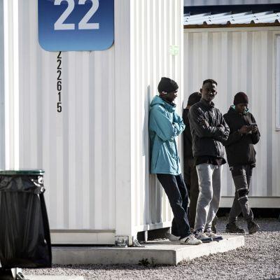 Leirin asukkaat odottelevat väliaikaisten majoitustilojen edustalla.