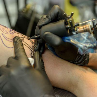 En person tatueras med en tatueringsmaskin.