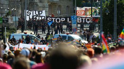 Motdemonstranter samlas bredvid personer som marscherar i prideparaden.