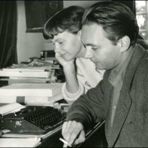 Stig Dagerman röker vid en skrivmaskin. Kvinna ler bredvid honom.