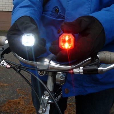 Pyöräilijä esittelee pyöränsä valoja.