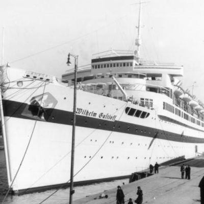 Mustavalkoinen kuva valkoisesta aluksesta laiturissa.