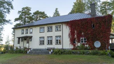 En äldre träbyggnad med vildvin växer på en del av fasaden.