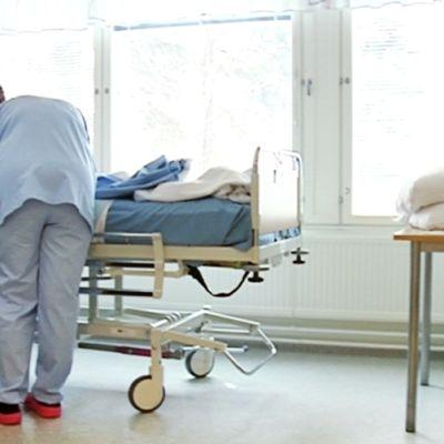 Kaksi hoitajaa sairassängyn luona.