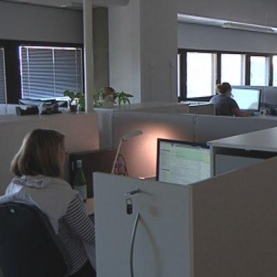 Naisia työskentelee pöytien ääressä viisumipalvelukeskuksessa.