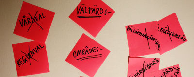 Post-it lappar på en vägg där det står välfärdsområdesval, och vårdval och regionval.