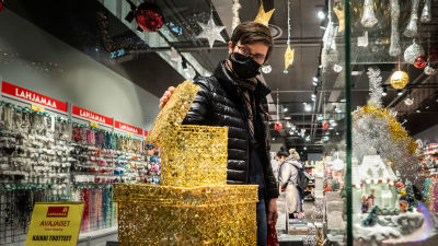 Nainen katselemassa lahjoja joulukaupassa.