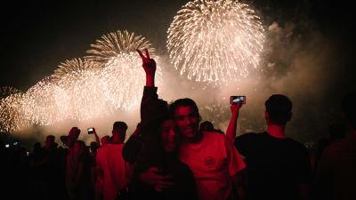 Människor poserar för kameror medan fyrverkerier syns på himlen i New York 4.7.2021.