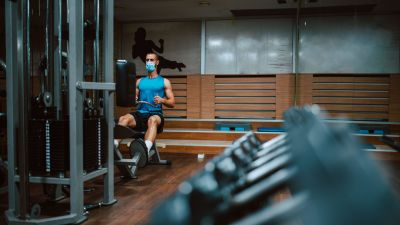 En man i munskydd tränar på gym.
