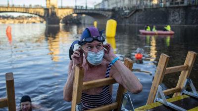 Uimari nousee joesta tikkaita pitkin ja laittaa maskia kasvoilleen