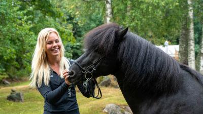 Arnella Nyman bredvid sin mörkbruna islandshäst Thór utomhus i en grön miljö.