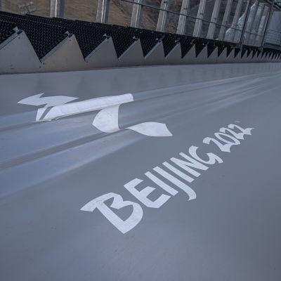 Nedre delen av en hoppbacke med Peking-OS logo i mitten.