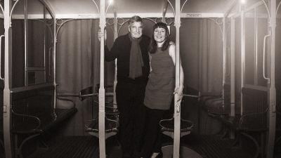 En svartvit bild på Claes Anderson tillsammans med Julia Korkman. De står bredvid varandra och med armarna över varandras axlar.