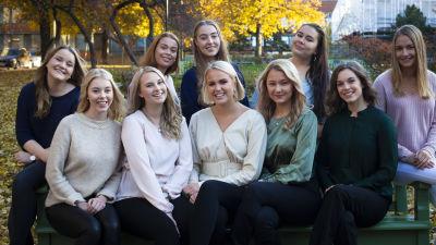 Luciakandidaterna 2019 sitter och står kring en parkbänk. Luciakandidaterna 2019. Från vänster sittande: Julia Wik, Felicia Holländer, Melissa SUndblad, Nea Lundström, Moa Björklund, Sara Ray, Jessica Lindholm. Uppe Minette Bäckblom, Wilma Rehnst
