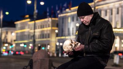 Lukupiirin toimittaja Jukka Kuosmanen istuu Helsingin keskustassa Keisarinnan kivellä Kauppatorilla aikaisin aamupimeydessä pääkallo käsissään