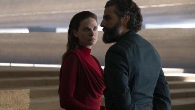 rebecca ferguson i röd klänning framför svartklädd Oscar Isaac  som sngelar över hennes axel.