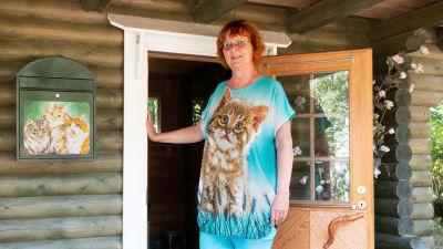 En kvinna vid ett stockhus, bredvid henne på väggen en postlåda med tre katter målade på.