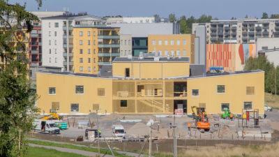 Ett nyt daghem i gult och en massa höghus i bakgrunden.