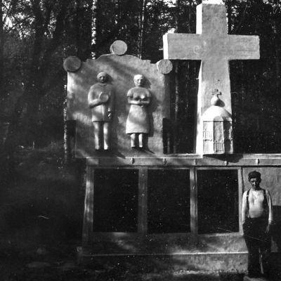 Mies seisoo suuren patsaan edessä.