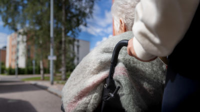 En äldre person i rullstol i Gårdsbacka i Helsingfors.