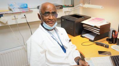 Läkare i vit rock sitter vid ett skrivbord.