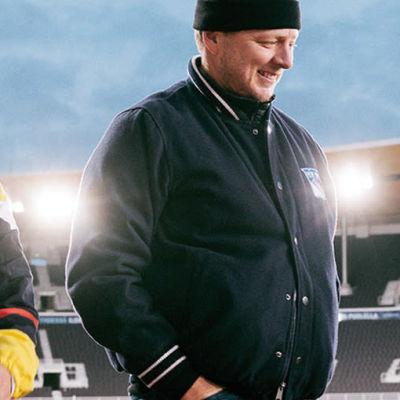 Kolme ihmistä kävelee Olympiastadionin kentällä.