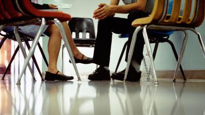Två personer som sitter mot varandra. Bilden är beskuren så att endast nedre delen av kroppen syns.