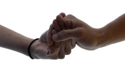 Två män håller hand.
