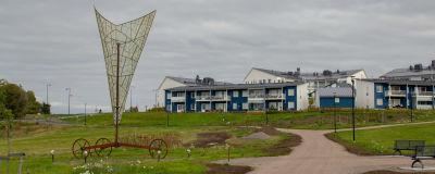 Ett högt konstverk som ser ut som ett segel från en båt, det står på tre hjul. I bakgrunden syns blåa bostadshus.