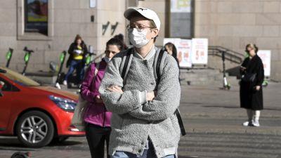 En person iförd munskydd i centrala Helsingfors.