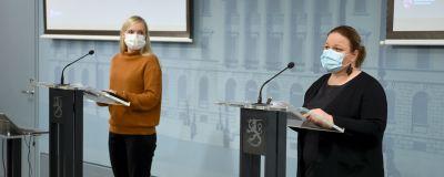 Maria Ohisalo och Krista Kiuru står vid var sitt podium på en presskonferens.