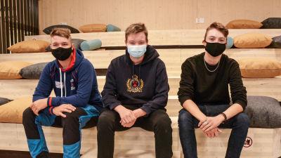 Tre unga män med munskydd sitter på en trätrappa.