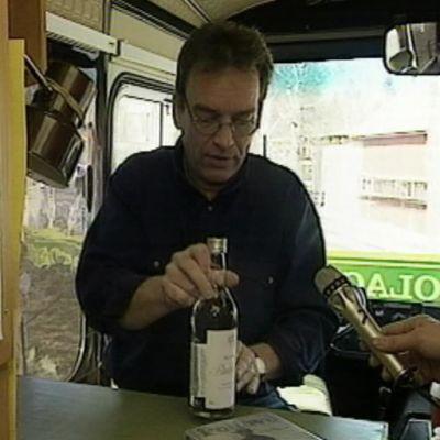 Mies laittaa viinapullon tiskille.