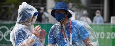 Personal vid OS i Tokyo pratar utomhus. De har på sig regnrockar och munskydd.