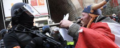 En man inklädd i den franska seriekaraktären Obelix höjer händerna mot en beväpnad och maskerad polis.