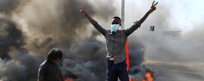 Unga sudanesiska demonstranter blockerade gator i Khartoum med brinnande bildäck.