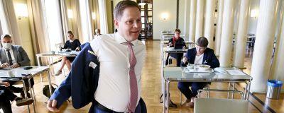 En man sätter på en kostymjacka på ett café.