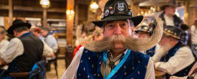 En man med stor mustasch och en hatt på huvudet. Han är en av deltagarna i skägg-OS i den tyska staden Eging am See i oktober, 2021.