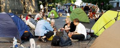 Demonstranter sitter på gatan bland tält.