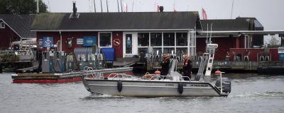 En båt kör framför en röd stuga på Skifferholmen utanför Helsingfors.