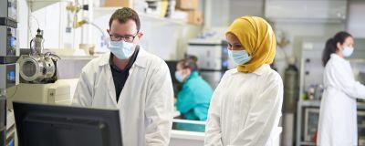 En man och en kvinna i labbrockar står vid en dator i ett laboratorium. De bär båda munskydd. I bakgrunden syns två andra kvinnor i munskydd.