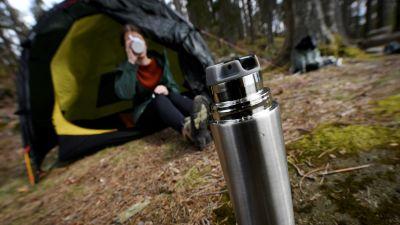 En kvinna sitter halvt inne i ett tält i skogen och för en mugg till munnen. I förgrunden en öppnad termos.