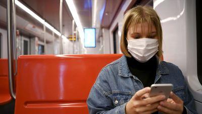 En ung kvinna sitter i metron i Helsingfors. Hon bär munskydd och tittar ner på sin mobil.