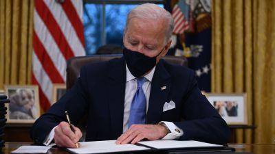 Joe Biden sitter i Ovala rummet i Vita huset och signerat presidentdekret.