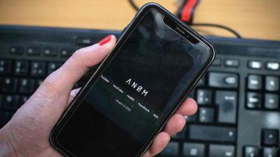 """En närbild på en svart mobil med texten """"ANOM""""."""