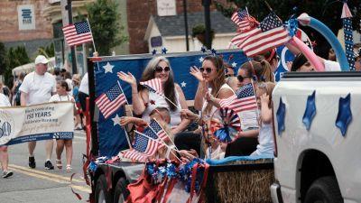 Bilparad under självständighetsfirandet i USA. Människor viftar med flaggor.