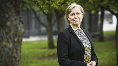 Maija Sakslin iklädd kavaj står i en park, halvkroppsbild.