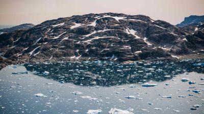 Isflak eller isberg i havet framför en delvis snötäckt klippa eller ett berg. Östra Grönland den 15 augusti 2019.