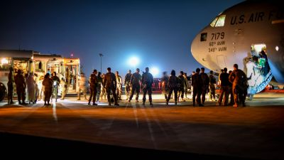 Upplyst flygplats där människor kliver ut ur ett flygplan på väg till väntande bussar. Evakuerade afghaner landar i Kuwait den 24 augusti.